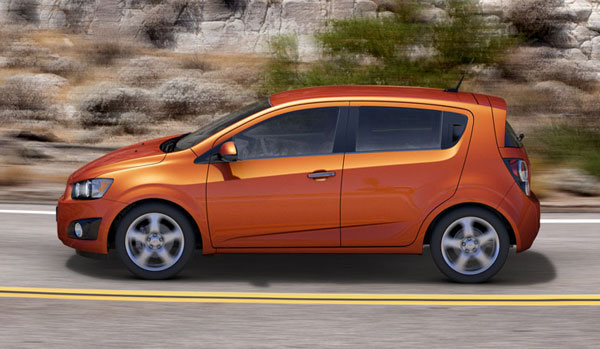 orange 2013 chevrolet sonic Exterior - in motion.
